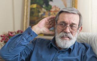 Hörverlust im Alter frühzeitig erkennen. Senior mit Hand am Ohr.