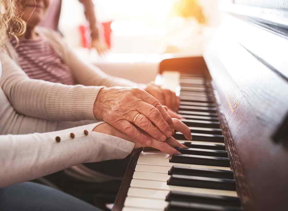 Ältere Senioren mit Enkelin am Klavier